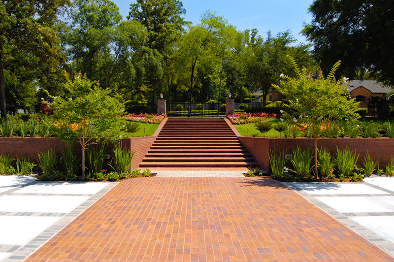Large brick stair case running to main entrance gate with landscaping