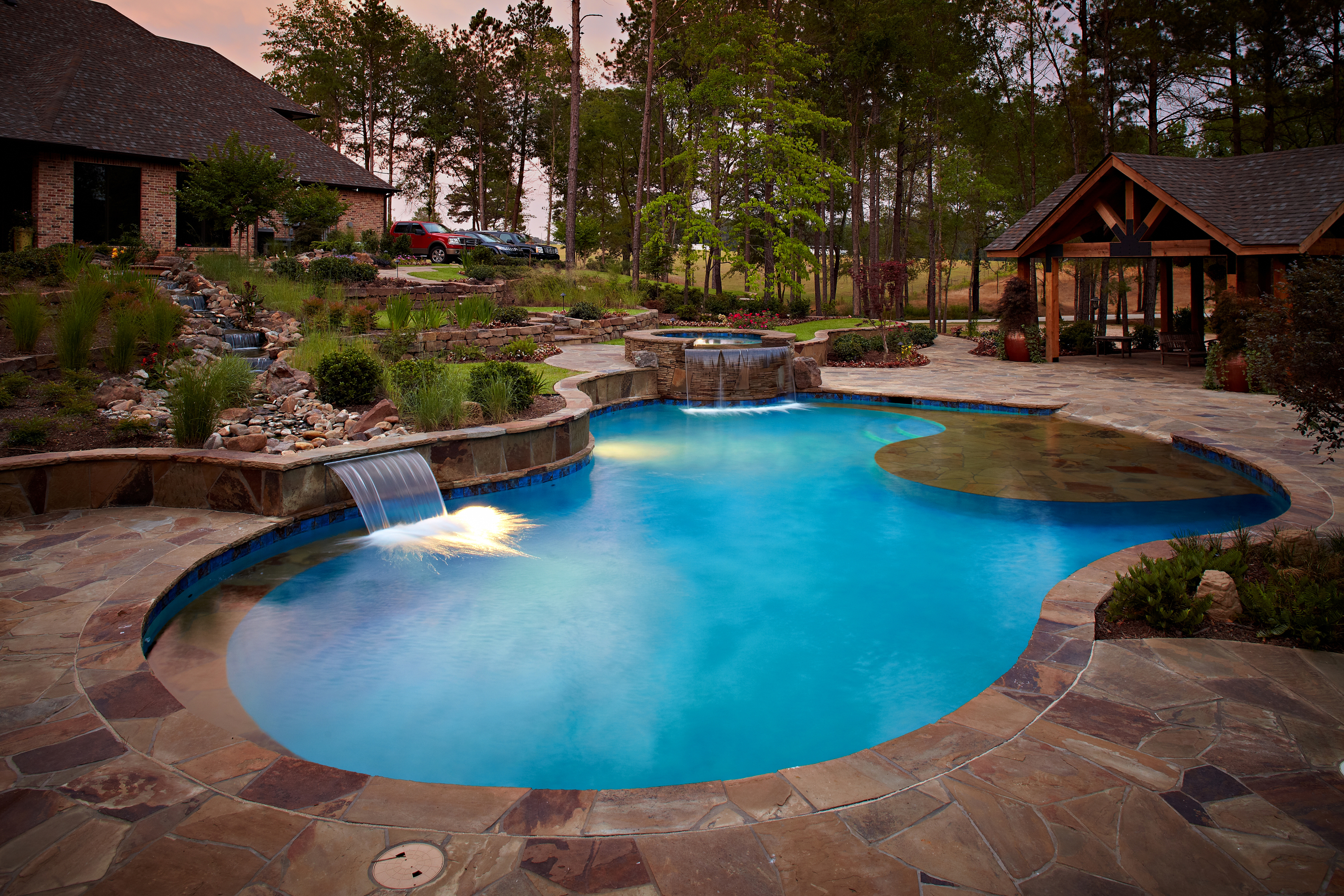 River rock river flowing down into pool designed by CCH Pools, landscaping done by Tucker and Associates
