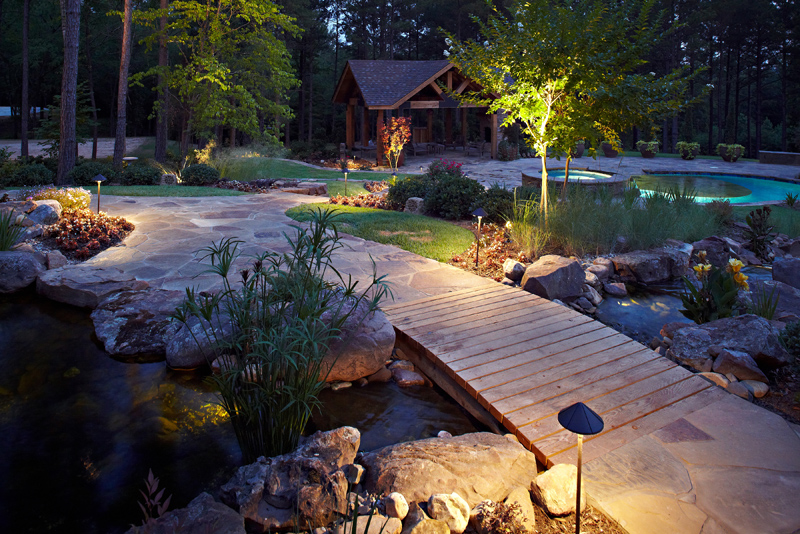 nighttime shot of landscape lighting provided by tucker and associates highlighting a stone pathway around a pool and outdoor living space