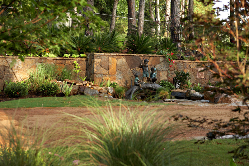 Large stone retaining wall with coy pond, bronze sculpture of 3 kids fishing on a log, and beautiful landscaping